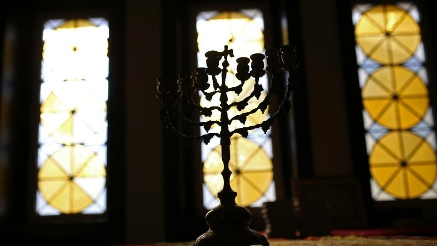In this photo taken on Tuesday, May 5, 2015, a nine-branched Jewish candelabrum, or Hanukkah Menorah, rests on a table in the main Jewish synagogue in Lisbon. Portugal enacted in March a law to grant citizenship to descendants of Sephardic Jews exiled during the Inquisition 500 years ago. Spain is about to adopt a similar law but its different requirements have brought criticism. (AP Photo/Francisco Seco)