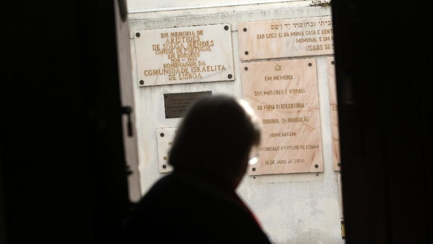 "In this photo taken on Tuesday, May 5, 2015, a jewish woman walks past memorials stones at the main Jewish synagogue in Lisbon. Portugal enacted in March a law to grant citizenship to descendants of Sephardic Jews exiled during the Inquisition 500 years ago. Spain is about to adopt a similar law but its different requirements have brought criticism.The stone on the right below reads in Portuguese: ""In memory of martyrs and victims of the furiously persecution of the Inquisition. Tribute by the Jewish community of Lisbon. May 18, 2004"". (AP Photo/Francisco Seco)"