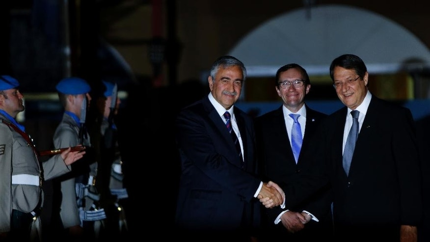 Cyprus' president Nicos Anastasiades, right, and Turkish Cypriot leader Mustafa Akinci shake hands as the United Nations envoy Espen Barth Eide, center, smiles before a dinner at the Ledra Palace Hotel inside the UN controlled buffer zone that divides the Cypriot capital Nicosia, on Monday, May 11, 2015. The dinner is the first meeting between Anastasiades and Akinci since the Turkish Cypriot politician _ a left-wing moderate _ soundly defeated the hard-line incumbent in an election last month. Cyprus was split in 1974 when Turkey invaded after a coup by supporters of union with Greece. (AP Photo/Petros Karadjias)