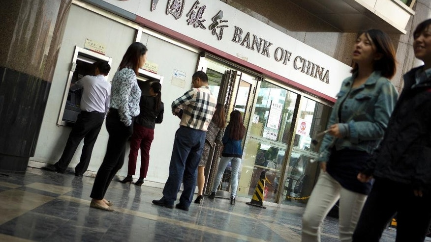 People walk past a Bank of China branch as customers wait to use ATMs in Beijing Monday, May 11, 2015. Bank of China is one of several large, state-owned Chinese banks that has been identified, in U.S. lawsuits and investigations, as facilitating credit card payments for online sales of fake goods or holding accounts for alleged counterfeiters. (AP Photo/Mark Schiefelbein)