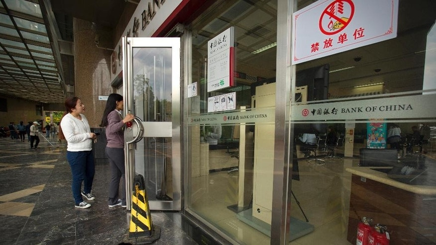 Customers walk into a Bank of China branch in Beijing Monday, May 11, 2015. Bank of China is one of several large, state-owned Chinese banks that has been identified, in U.S. lawsuits and investigations, as facilitating credit card payments for online sales of fake goods or holding accounts for alleged counterfeiters. (AP Photo/Mark Schiefelbein)