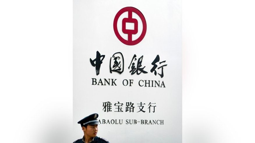 A security guard stands outside a Bank of China branch in Beijing, Monday, May 11, 2015. Bank of China is one of several large, state-owned Chinese banks that has been identified, in U.S. lawsuits and investigations, as facilitating credit card payments for online sales of fake goods or holding accounts for alleged counterfeiters. (AP Photo/Mark Schiefelbein)