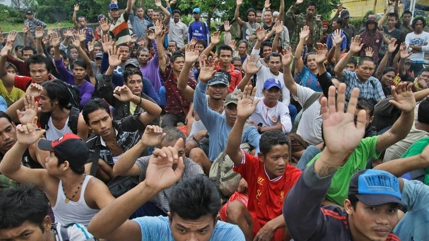 FILE - In this April 3, 2015 file photo, rescued Burmese fishermen raise their hands as they are asked who among them wants to go home at the compound of Pusaka Benjina Resources fishing company in Benjina, Aru Islands, Indonesia. Two Indonesians and five Thais were arrested on charges of human trafficking connected with slavery in the seafood industry, Indonesian police said Tuesday, May 12. They were the first suspects taken into custody since the case was revealed by The Associated Press in a report two months ago. The arrests were made Monday and late Friday in the remote island village of Benjina, said Lt. Col. Arie Dharmanto, National Police anti-trafficking unit chief. (AP Photo/Dita Alangkara, File)