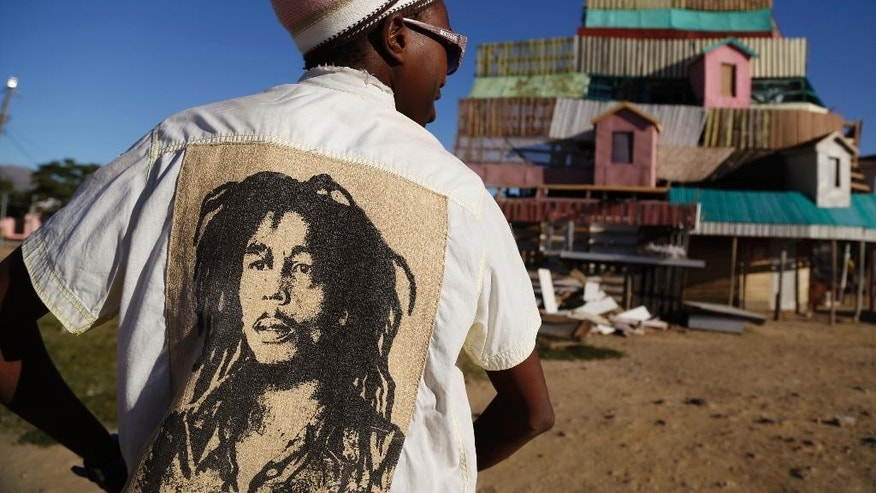 A Rastafarian wearing a shirt showing the face of Jamaican reggae singer Bob Marley, stands near a five storey high handmade wooden structure in Paarl, South Africa, Monday May 11, 2015. Twelve people have made the building their home, some rooms are areas of worship, others bedrooms, and another a communal meeting place open to visiting Rastafarians. (AP Photo/Schalk van Zuydam)