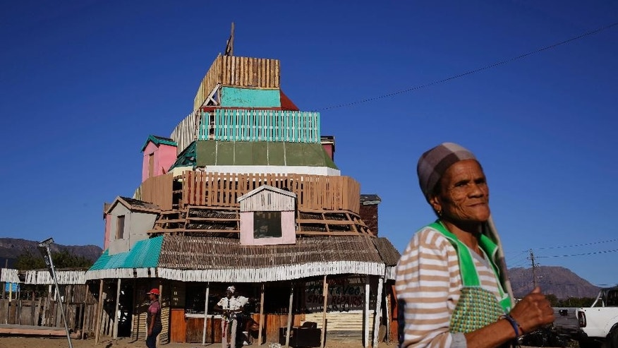 A woman walks past the Rastafarian owned five storey high, handmade wooden structure in Paarl, South Africa, Monday May 11, 2015. Twelve people have made the building their home, some rooms are areas of worship, others bedrooms, and another a communal meeting place open to visiting Rastafarians. (AP Photo/Schalk van Zuydam)
