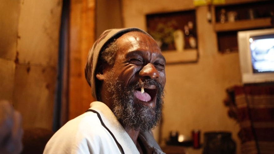 A Rastafarian laughs inside the Rastafarian owned five storey high, handmade wooden structure in Paarl, South Africa, Monday May 11, 2015. Twelve people have made the building their home, some rooms are areas of worship, others bedrooms, and another a communal meeting place open to visiting Rastafarians. (AP Photo/Schalk van Zuydam)