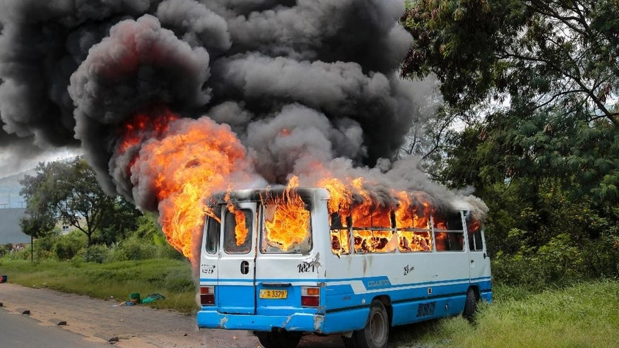 A bus burns after being set on fire by demonstrators in the Ngagara district of Bujumbura, Burundi Tuesday, May 12, 2015. A crowd who were marching to the funeral of a woman who died in recent protests were blocked from doing so by police, and the crowd then set fire to a bus and government car and motorcycle. (AP Photo/Berthier Mugiraneza)