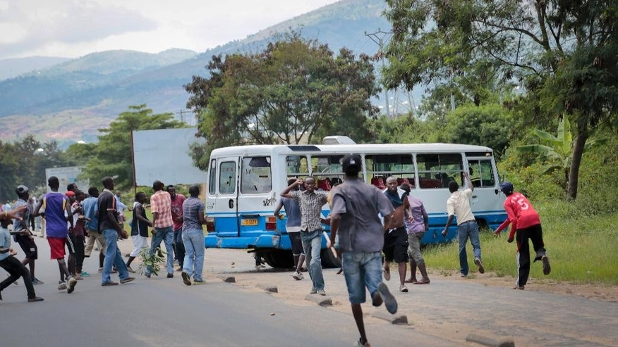 Demonstrators smash the windows of a bus before burning it in the Ngagara district of Bujumbura, Burundi Tuesday, May 12, 2015. A crowd who were marching to the funeral of a woman who died in recent protests were blocked from doing so by police, and the crowd then set fire to a bus and government car and motorcycle. (AP Photo/Berthier Mugiraneza)