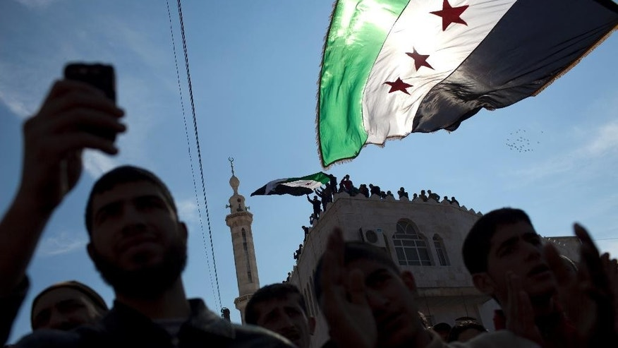 FILE - In this Friday, March 2, 2012 file photo, men hold revolutionary Syrian flags during an anti-government protest in a town in northern Syria. A dispute erupted on Tuesday, May 12, 2015, among the Syrian opposition after a press conference where the Khaled Khoja, leader of the Syrian National Coalition, decided not to display the flag that for the past four years many have adopted as the symbol of their rebellion - a green, white and black flag with three red stars - after another opposition figure argued it was divisive. The official Syrian flag is red, white and black with two green stars in the center. (AP Photo/Rodrigo Abd, File)