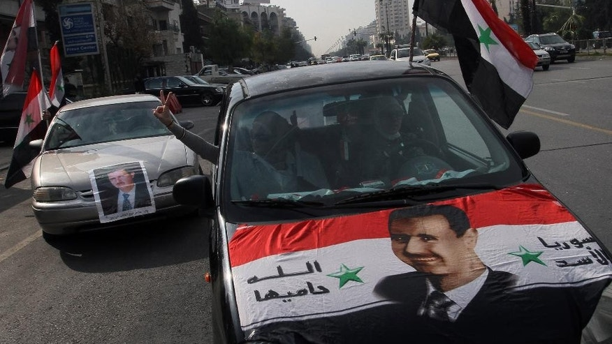 "FILE - In this Wednesday, Jan. 22, 2014 file photo, Syrians display national flags and banners with photos of Syrian President Bashar Assad during a pro-government event in Damascus, Syria. A dispute erupted on Tuesday, May 12, 2015, among the Syrian opposition after a press conference where the Khaled Khoja, leader of the Syrian National Coalition, decided not to display the flag that for the past four years many have adopted as the symbol of their rebellion - a green, white and black flag with three red stars - after another opposition figure argued it was divisive. The official Syrian flag is red, white and black with two green stars in the center. Arabic on the banner reads, ""Syria is for Assad, God will protect it."" (AP Photo, File)"