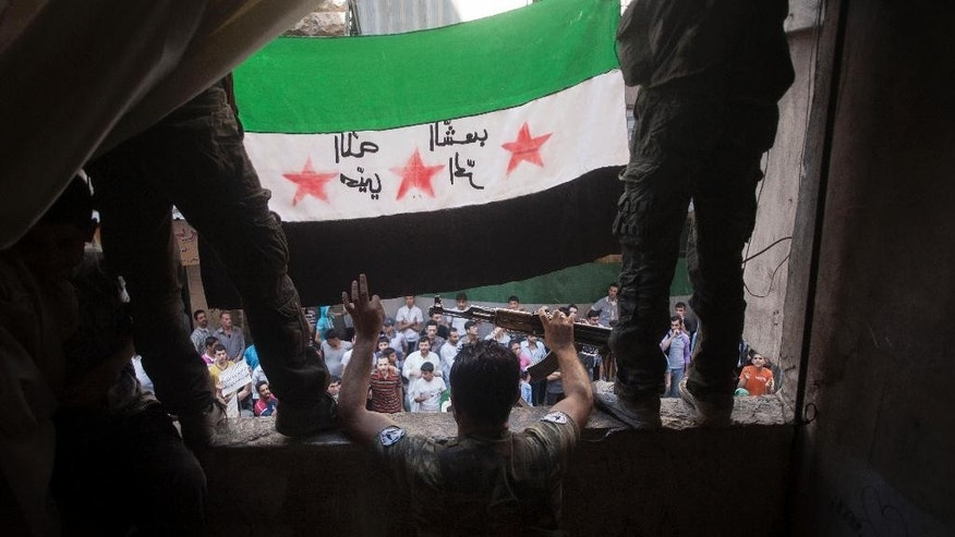 "FILE - In this Friday, Sept. 21, 2012 file photo, Free Syrian Army rebels hold a revolutionary flag during a demonstration in the Bustan al-Qasr neighborhood of Aleppo, Syria. A dispute erupted on Tuesday, May 12, 2015, among the Syrian opposition after a press conference where the Khaled Khoja, leader of the Syrian National Coalition, decided not to display the flag that for the past four years many have adopted as the symbol of their rebellion - a green, white and black flag with three red stars - after another opposition figure argued it was divisive. The official Syrian flag is red, white and black with two green stars in the center. Arabic on the flag is reversed, but reads, ""God welcome, free people."" (AP Photo/Manu Brabo, File)"