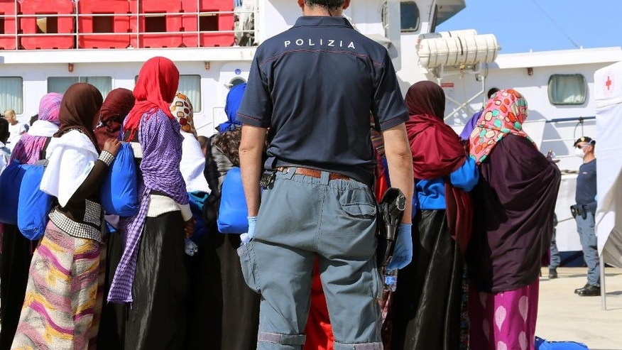 A police officer watches migrants disembarking from the Offshore Aid Station vessel ' Phoenix ' in the harbor of Augusta, Sicily, Southern Italy, Saturday, May 9, 2015. Ireland and France are the latest European Union nations answering Italy's pleas for help with the rescue of migrants' who are risking their lives on smugglers' boats in the Mediterranean. (AP Photo/Francesco Malavolta)