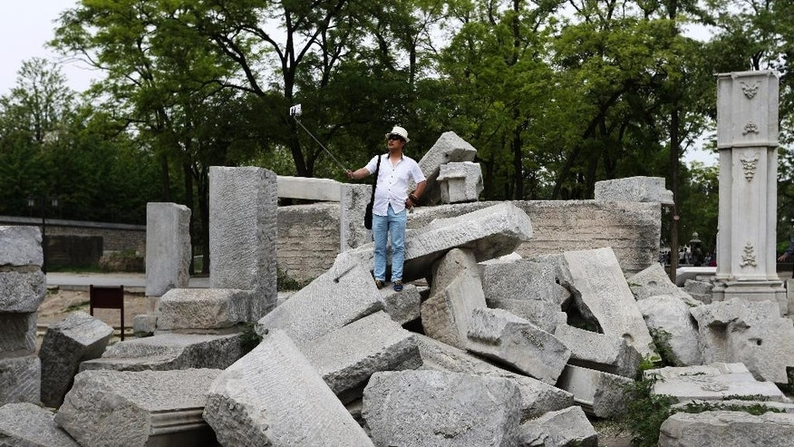 "In this May 6, 2015 photo, Liu Yaming uses a selfie stick to take souvenir photo of himself at the ruined Old Summer Palace on the outskirts of Beijing. China already has its own copies of London's Tower Bridge and the Eiffel Tower. Now a life-sized model by a film studio of one of the country's own historical attractions - the Old Summer Palace - has ruffled the bosses of the original garden of emperors.  Liu say rebuilding the site showed ""a kind of ignorance of our national humiliation."" (AP Photo/Andy Wong)"