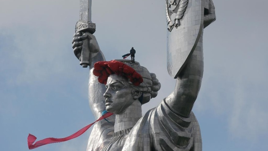 FILE - In this Friday, May 8, 2015, file photo, a worker installs a wreath of poppies as a red peak, and red ribbon on top of the 102-meter Motherland Monument in Kiev, Ukraine, to mark the anniversary of the defeat of the Nazis in World War II. The Motherland Monument's shield bears the Communist hammer-and-sickle _ but maybe not for much longer. Ukraine's leaders are eager to be seen as reinventing the nation and erasing all visible reminders of the communist past, they say, is an important step toward that goal. (AP Photo/Efrem Lukatsky, File)