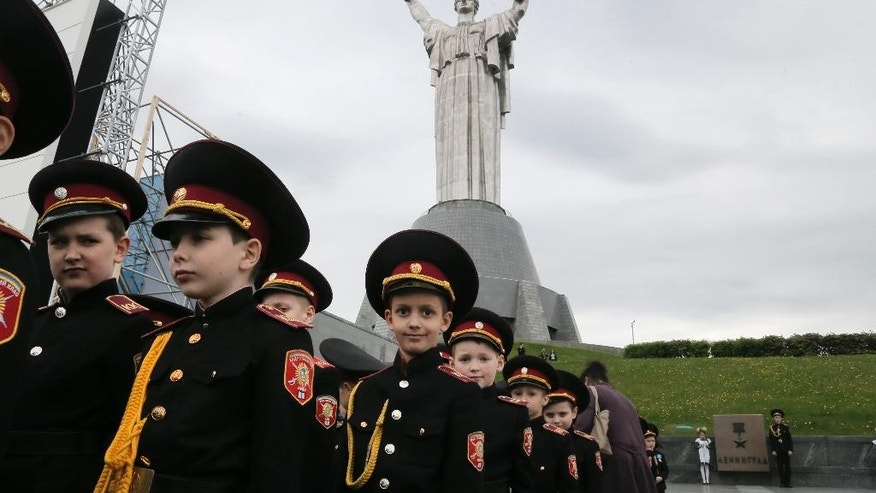 In this photo taken Tuesday May 5, 2015, cadets march in a parade of the Kiev military schools in preparation for Victory Day, with the Motherland Monument in the background, at the WWII memorial in Kiev, Ukraine. The Motherland Monument's shield bears the Communist hammer-and-sickle _ but maybe not for much longer. Ukraine's leaders are eager to be seen as reinventing the nation and erasing all visible reminders of the communist past, they say, is an important step toward that goal. (AP Photo/Efrem Lukatsky)