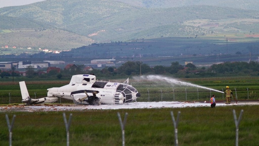 Fire fighter sprays foam onto a helicopter belonging to a European Union mission in Kosovo, after it has crashed during a training flight, at the country's main airport, injuring one member of the mission, Kosovo airport spokeswoman Valentina Gara said in Slatina, Kosovo, Tuesday May 12, 2015. The mission, known as EULEX helps Kosovo authorities fight organized crime, corruption and war crimes committed during the 1998-99 Kosovo war. (AP Photo/Visar Kryeziu)