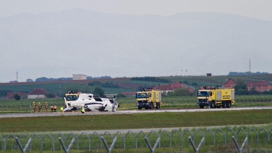 Fire fighter and airport officials attend the scene after a helicopter belonging to a European Union mission in Kosovo, crashed during a training flight, at the country's main airport, injuring one member of the mission, Kosovo airport spokeswoman Valentina Gara said in Slatina, Kosovo, Tuesday May 12, 2015. The mission, known as EULEX helps Kosovo authorities fight organized crime, corruption and war crimes committed during the 1998-99 Kosovo war. (AP Photo/Visar Kryeziu)