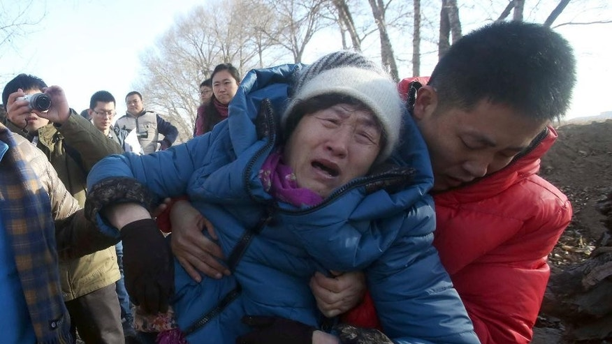 FILE - In this Dec. 15, 2014 photo, the brother of Huugjilt, a wrongly executed man, holds his grieving mother during a visit to Huugjilt's tomb in Hohhot in northern China's Inner Mongolia Autonomous Region. Huugjilt, who was 18 when he was convicted and executed in 1996 on charges of rape and murder, was formally exonerated by the Chinese government in Dec. 2014, and the police officer who oversaw the original case has been charged with using torture to coerce a confession. In a report released Wednesday, May 13, 2015, Human Rights Watch says that police abuse in order to extract confessions continues to be a serious problem despite measures to reform the legal system. (Chinatopix via AP) CHINA OUT