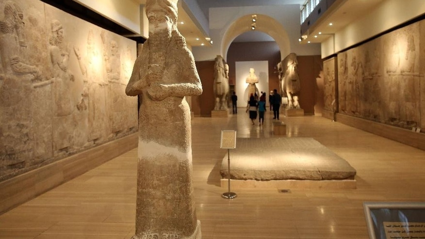 March 15, 2015: People observe ancient artifacts at the Iraqi National Museum after its reopening in the wake of the recent destruction of Assyrian archaeological sites by the Islamic State group in Mosul, as they visit the museum in Baghdad.