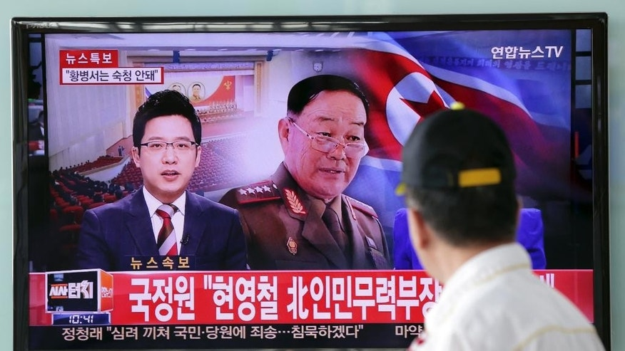 "A man watches a TV news program reporting that North Korean People's Armed Forces Minister Hyon Yong Chol was killed by anti-aircraft gunfire, at Seoul Railway Station in Seoul, South Korea, Wednesday, May 13, 2015. North Korean leader Kim Jong Un executed his defense chief for sleeping during a meeting and talking back to the young leader, South Korea's spy agency told lawmakers Wednesday, citing what it called credible information. The part of letters on the bottom ""National Intelligence Service, North Korea's People's Armed Forces Minister Hyon Yong Chol."" (AP Photo/Lee Jin-man)"