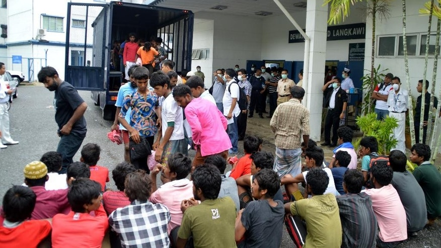 FILE - In this Monday, May 11, 2015, file photo, Illegal immigrants from Myanmar and Bangladesh arrive at the Langkawi police station's multi purpose hall in Langkawi, Malaysia. As a crisis involving boatloads of Rohingya and Bangladeshi migrants stranded at sea deepened, Malaysia said Tuesday it would turn away any more of the crowded, wooden vessels unless they were sinking. (AP Photo/Hamzah Osman, File)
