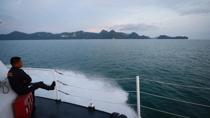Malaysia's maritime enforcement agency official rest on their patrolling boat along the coast of Langkawi Island, Malaysia, on Tuesday, May 12, 2015. A crisis involving boatloads of Rohingya and Bangladeshi migrants stranded at sea deepened Tuesday as Malaysia said it would turn away any more of the crowded, wooden vessels unless they were sinking. (AP Photo/Vincent Thian)