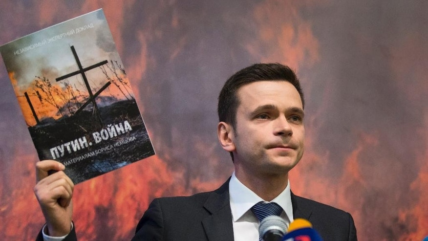 Russian opposition figure Ilya Yashin holding a report by slain Russian opposition leader Boris Nemtsov speaks to the media in Moscow, Russia, Tuesday, May 12, 2015. A report released Tuesday containing material compiled by slain Russian opposition leader Boris Nemtsov said at least 220 Russian soldiers died in two battles in eastern Ukraine within the past year. (AP Photo/Alexander Zemlianichenko)