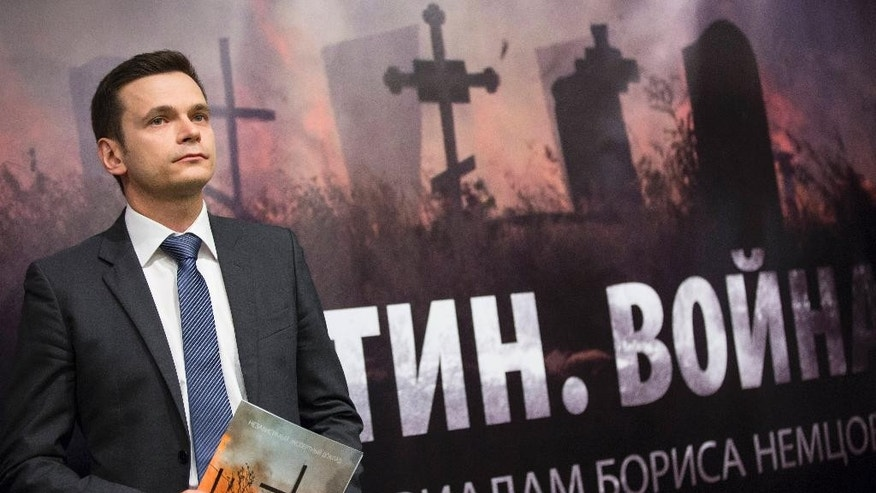 Russian opposition figure Ilya Yashin holding a report by slain Russian opposition leader Boris Nemtsov speaks to the media in front of a poster that reads 'Putin. War.' in Moscow, Russia, Tuesday, May 12, 2015. A report released Tuesday containing material compiled by slain Russian opposition leader Boris Nemtsov said at least 220 Russian soldiers died in two battles in eastern Ukraine within the past year. (AP Photo/Alexander Zemlianichenko)