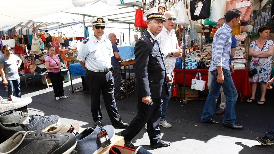 "Gen. Pietro Belfiore of the local police in Catania, Sicily, southern Italy, center, walks past market's stands, Friday, May 8, 2015. When migrants arrive in Italy, exhausted after days of perilous travel in overcrowded boats, one of the first things they receive is a pair of shoes. The gleaming sneakers stand out incongruously against the migrants' clothes, grimy and threadbare from days of travel. ""The phenomenon of counterfeit sales is run by non-Europeans, mostly Senegalese,"" says Gen. Pietro Belfiore of the local police in Catania, a city on the east coast of Sicily that lies between the sea and the foothills of volcanic Mt. Etna. (AP Photo/Antonio Calanni)"