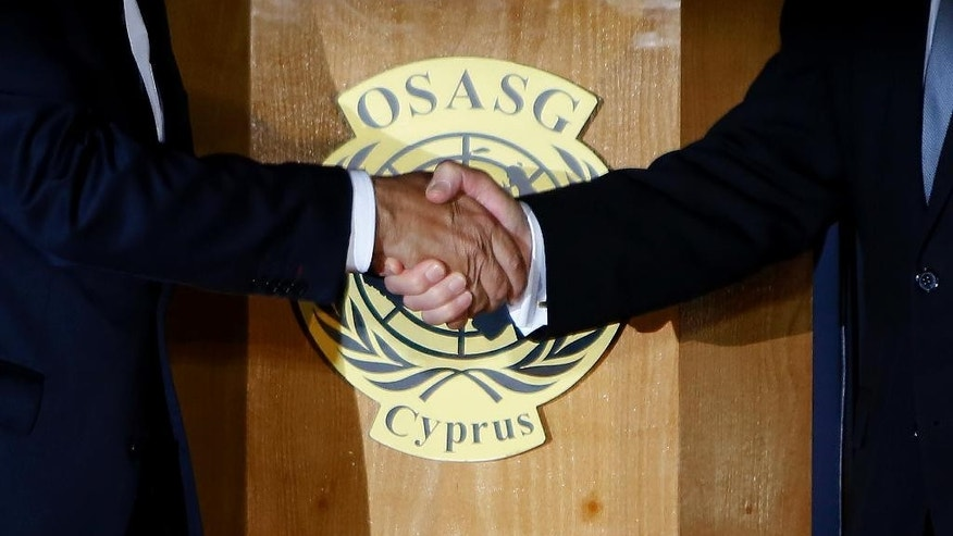 Cyprus' president Nicos Anastasiades, right, and Turkish Cypriot leader Mustafa Akinci, left, shake hands after a dinner at the Ledra Palace Hotel inside the UN controlled buffer zone that divides the Cypriot capital Nicosia, on Monday, May 11, 2015. The leaders of ethnically divided Cyprus' rival Greek and Turkish speaking communities will relaunch stalled talks aimed at reunifying the island on May 15, a United Nations envoy said. Cyprus was split in 1974 when Turkey invaded after a coup by supporters of union with Greece. (AP Photo/Petros Karadjias)
