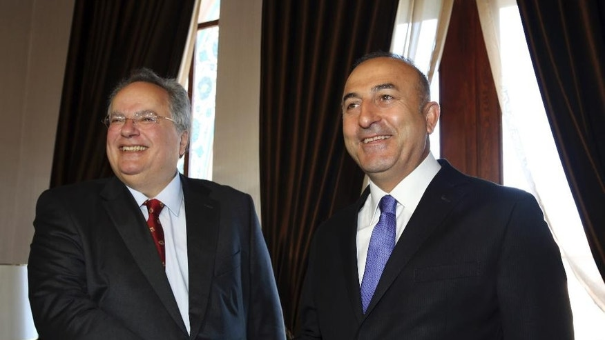 Turkish Foreign Minister Mevlut Cavusoglu, right, shakes hands with his Greek counterpart Nikos Kotzias prior to their meeting in Ankara, Turkey, Tuesday, May 12, 2015. Kotzias is in Turkey on an official visit. (AP Photo/Burhan Ozbilici)