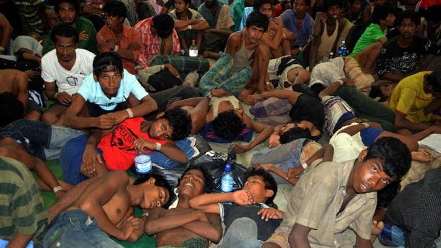 May 11, 2015: Illegal immigrants from Burma and Bangladesh arrive at the Langkawi police station's multipurpose hall in Langkawi, Malaysia. (AP Photo/Hamzah Osman)