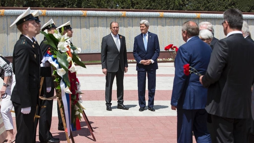 U.S Secretary of State John Kerry and Russian Foreign Minister Sergey Lavrov, center left, watch as members of the United States and Russian delegations place red flowers at the Zakovkzalny War Memorial in Sochi, Russia, Tuesday May 12, 2015. Kerry is in Russia to meet President Vladimir Putin with an eye on easing badly strained relations over conflicts in Ukraine and Syria. (Joshua Roberts/Pool Photo via AP)