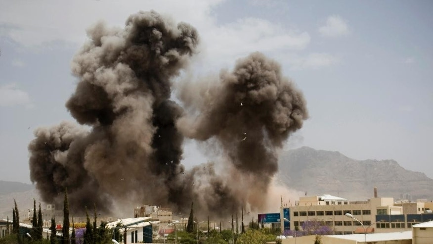 FILE - In this April 8, 2015 file photo, smoke billows from a Saudi-led airstrike in Sanaa, Yemen. Saudi Arabia is now leading an offensive against the Shiite Houthi rebels in Yemen, who are supported by its arch-rival Iran. Much of the kingdom, however, continues on its prosperous way, as reflected in interviews by The Associated Press with more than two dozen people. (AP Photo/Hani Mohammed, File)