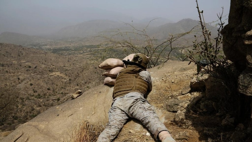 In this photo taken on April 20, 2015, a Saudi soldier aims his weapon toward the Yemen border in Jizan, Saudi Arabia. The country is now leading an offensive against the Shiite Houthi rebels in Yemen, who are supported by its arch-rival Iran. Much of the kingdom, however, continues on its prosperous way, as reflected in interviews by The Associated Press with more than two dozen people. (AP Photo/Hasan Jamali)