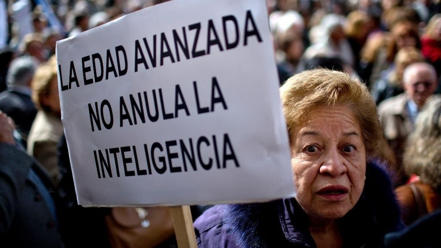 "A woman holds a sign that reads in Spanish ""Advanced age doesn't annul intelligence"" at a demonstration in defense of Supreme Court judge Carlos Fayt in Buenos Aires, Argentina, Wednesday, May 13, 2015. The government is questioning whether the 97-year-old judge is in good enough physical and mental condition to stay on the court, after it he didn't attend a court meeting that re-elected the head of the court. His fellow court members gave him their support Wednesday, saying he cast his vote and that those decisions can be signed inside or outside the court. (AP Photo/Natacha Pisarenko)"