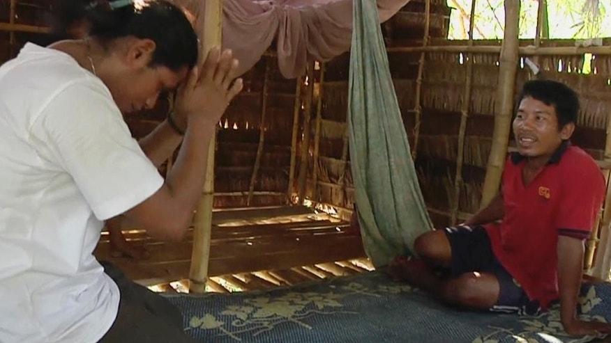 In this May 10, 2015, image made from video, former slave fisherman Kyaw Naing, left, pays respects after he is reunited with his brother Kyaw Oo at his home in Myaung Mya, Myanmar. Kyaw Naing, who was at one point kept in a cage on the remote island of Benjina, is among eight migrant fishermen rescued for their safety in the course of an Associated Press investigation into slavery in the seafood industry. Hundreds of others evacuated by the Indonesian government after the story are waiting to be repatriated. (AP Photo/APTN)