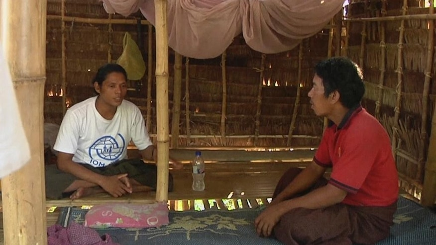 In this May 10, 2015, image made from video, former slave fisherman Kyaw Naing, left, talks with his brother Kyaw Oo after they were reunited at his home in Myaung Mya, Myanmar. Kyaw Naing, who was at one point kept in a cage on the remote island of Benjina, Indonesia, is among eight migrant fishermen rescued for their safety in the course of an Associated Press investigation into slavery in the seafood industry. Hundreds of others evacuated by the Indonesian government after the story are waiting to be repatriated. (AP Photo/APTN)