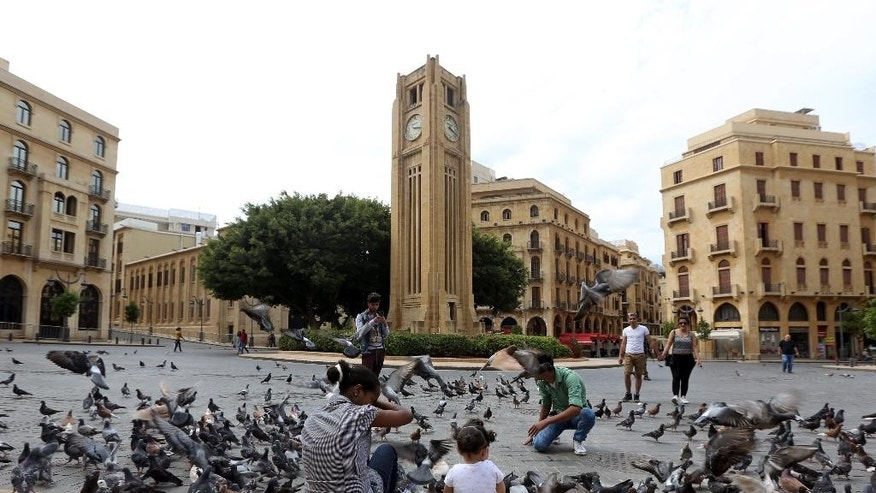 Lebanese feed pigeons near the four–faced Rolex clock tower at the Parliament square, in downtown Beirut, Lebanon, Wednesday, May 13, 2015. Not even tourists can set foot anywhere in the area during the twice-monthly lockdowns as lawmakers meet. On Wednesday, for the twenty-third time in a row, they failed to elect a president. (AP Photo/Bilal Hussein)
