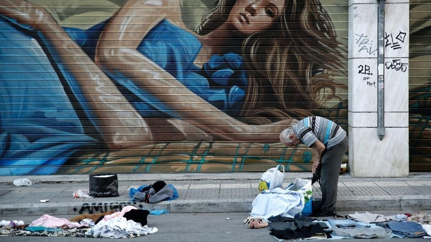 A street vendor collects his clothes outside the shutters of a shop in central Athens, early Wednesday, May 13, 2015.  Greece, which is in the midst of protracted bailout talks with creditors, is now officially in recession again according to data released Wednesday, less than a year after it emerged from a six-year depression. (AP Photo/Petros Giannakouris)