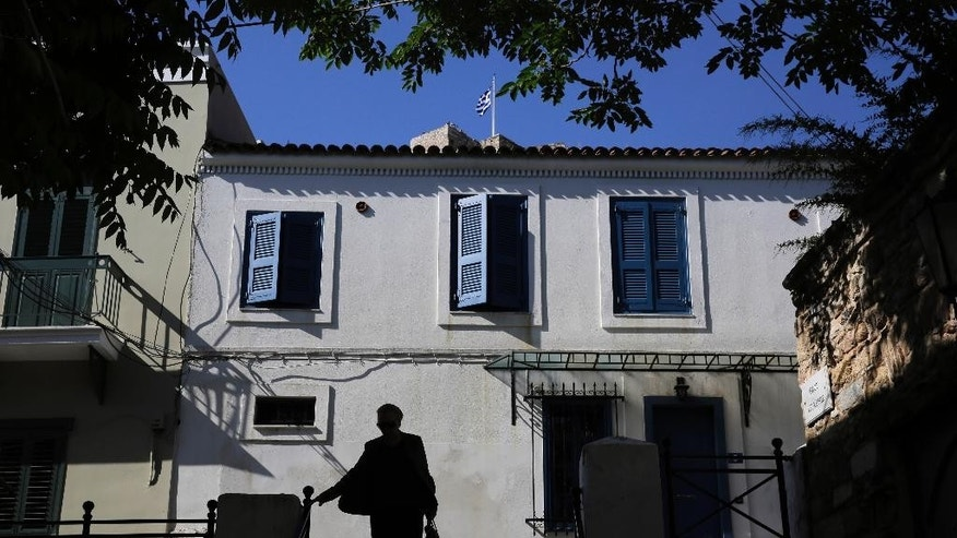 A woman walks in front of a house as a Greek flag flies atop the Acropolis hill of Athens, Wednesday May 13, 2015. Greece, which is in the midst of protracted bailout talks with creditors, is now officially in recession again according to data released Wednesday, less than a year after it emerged from a six-year depression. (AP Photo/Petros Giannakouris)