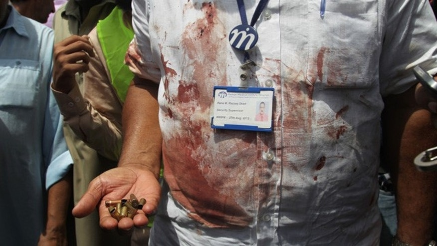 May 13, 2015: A Pakistani security official displays cartridges he collected from the scene of an attack on a bus in Karachi. Gunmen killed dozens of people on Wednesday aboard a bus in southern Pakistan bound for a Shiite community center, in the latest attack targeting the religious minority, police said. (AP Photo/Fareed Khan)