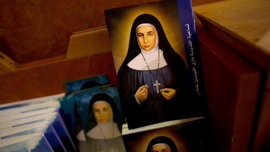 In this Thursday, May 7, 2015 photo, booklets showing the likes of Marie Alphonsine Ghattas, a nun who lived in what was Ottoman-ruled Palestine in the 19th century, are on display in Church of the Rosary Sisters Mamilla in Jerusalem. The Holy Land's Christians are excitedly preparing for next week's canonization of two Arab nuns, Ghattas and Mariam Bawardy, bringing some joy to a tiny community that has had little to celebrate in recent years. (AP Photo/Dusan Vranic)
