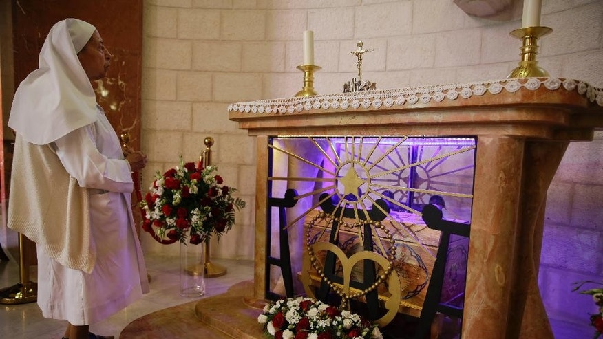 In this Saturday, May 9, 2015 photo, a nun stands by the tomb of Marie Alphonsine Ghattas, a nun who lived in what was Ottoman-ruled Palestine in the 19th century, at Church of the Rosary Sisters Mamilla in Jerusalem. Two nuns from the Holy Land, Mariam Bawardy and Marie Alphonsine Ghattas, will be the first from the region to receive sainthood since the early days of Christianity. They will also become the first Arabic-speaking Catholic saints. (AP Photo/Dusan Vranic)