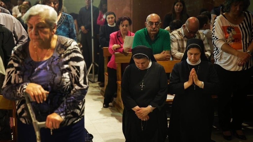 In this Saturday, May 9, 2015 photo, nuns pray during a special mass for Marie Alphonsine Ghattas, a nun who lived in what was Ottoman-ruled Palestine in the 19th century, at Church of the Rosary Sisters Mamilla in Jerusalem. Two nuns from the Holy Land, Mariam Bawardy and Marie Alphonsine Ghattas, will be the first from the region to receive sainthood since the early days of Christianity. They will also become the first Arabic-speaking Catholic saints. (AP Photo/Dusan Vranic)