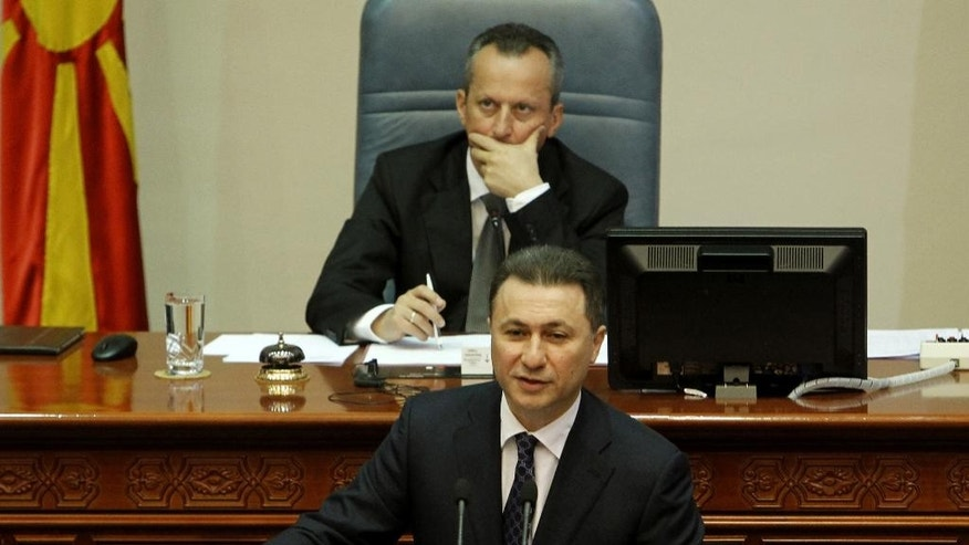 Macedonian Prime Minister Nikola Gruevski, bottom, addresses the lawmakers in presence of the speaker Trajko Veljanovski, top, during a session in the parliament after resignation of two ministers from Prime Minister's cabinet and a senior state security official, on Wednesday, May 13, 2015, in Skopje, Macedonia. Macedonian parliament has formally approved Wednesday the replacement of the interior and transport ministers in Prime Minister Nikola Gruevski's cabinet amid an escalating political crisis in the Balkan nation. Parliament approved the replacements in a 71-2 vote with one abstention. (AP Photo/Boris Grdanoski)