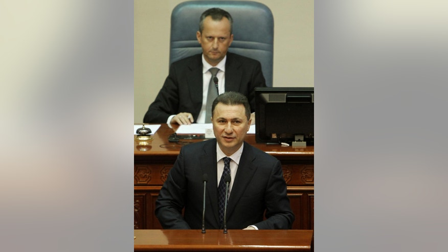 Macedonian Prime Minister Nikola Gruevski, bottom, addresses the lawmakers in presence of the speaker Trajko Veljanovski, top, during a session in the parliament after resignation of two ministers from Prime Minister's cabinet and a senior state security official, on Wednesday, May, May 13, 2015, in Skopje, Macedonia. Macedonian parliament has formally approved Wednesday the replacement of the interior and transport ministers in Prime Minister Nikola Gruevski's cabinet amid an escalating political crisis in the Balkan nation.Parliament approved the replacements in a 71-2 vote with one abstention. (AP Photo/Boris Grdanoski)