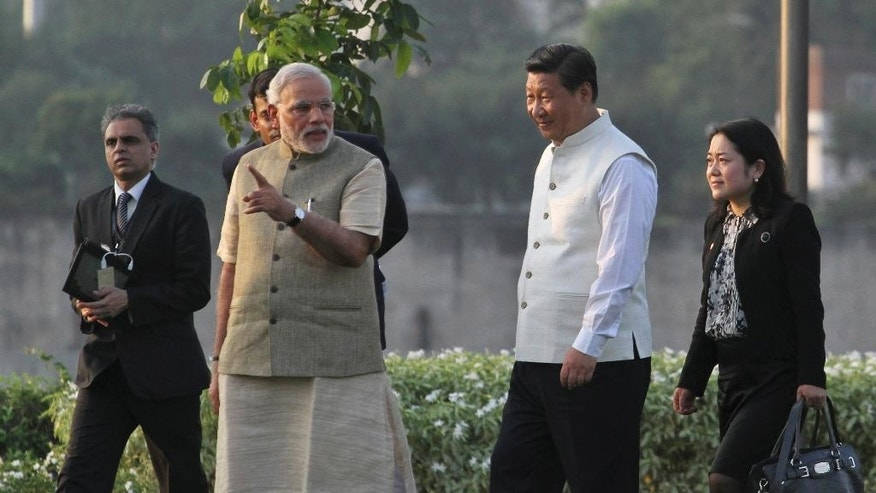FILE - In this Sept. 17, 2014 file photo, Indian Prime Minister Narendra Modi, second from left, talks to Chinese President Xi Jinping, second from right, as they walk on the Sabarmati River front in Ahmadabad, India. In a rare personal touch, Xi will host Modi in his hometown of Xi'an for the start of Modi's three-day visit on Thursday, May 14, 2015, highlighting warming ties between the Asian giants despite their continued rivalry and contrasting political systems. The move returns the favor after Modi hosted Xi in his own hometown of Ahmadebad in 2014. The two men will aim to move beyond the symbolism and take substantial steps to seal a new spirit of cooperation. (AP Photo/Ajit Solanki, File)