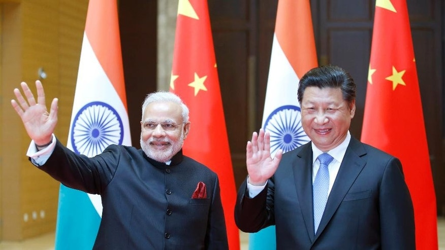 Indian Prime Minister Narendra Modi, left, and Chinese President Xi Jinping wave to journalists prior to their meeting in Xian, Shaanxi province, China, Thursday, May 14, 2015. Modi is visiting China this week to build friendship between the two Asian giants despite a long history of disputes and rivalries, along with some areas of cooperation, especially in the economic sphere. (Kim Kyung-Hoon/Pool Photo via AP)