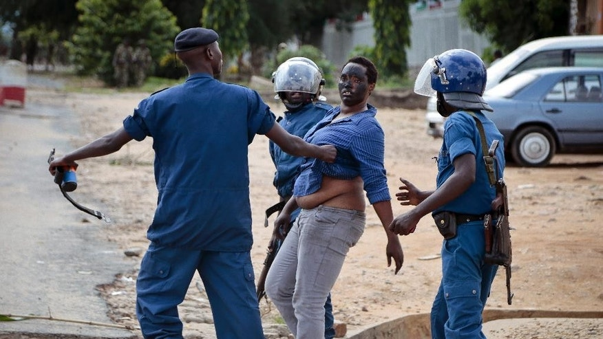 A demonstrator trying to march to the town center is arrested by police, in the Ngagara district of Bujumbura, Burundi Wednesday, May 13, 2015. A police officer opened fire at protesters in Burundi's capital Wednesday as demonstrations against the president's bid for a third term heated up, with troops surrounding the national radio station. (AP Photo/Gildas Ngingo)